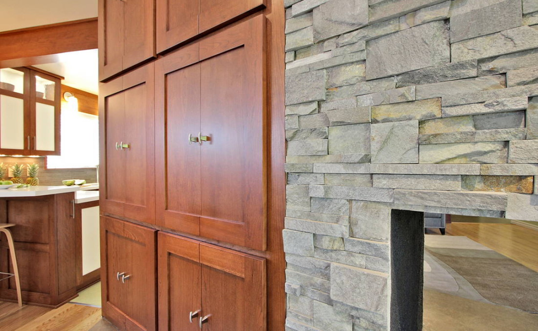 Cherry Cabinets Next to Stacked Stone Fireplace